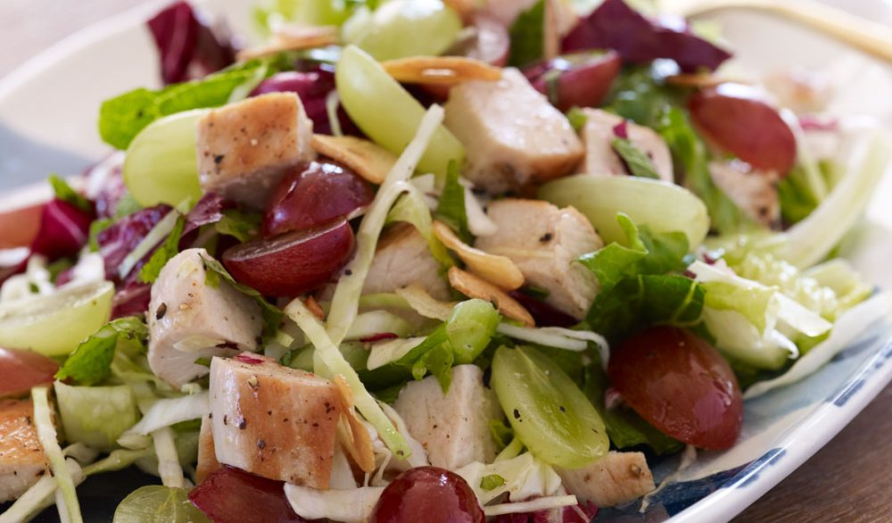 crispy chopped chicken with grapes on top of lettuce