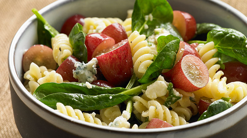 Pasta salad in bowl with rotini, red grapes and spinach