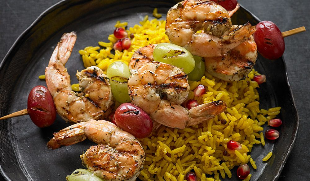 shrimp and green grapes on skewers with yellow rice on cast iron skillet